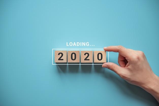 Laden des neuen jahres 2020 mit der hand, die holzwürfel in fortschrittsstange einsetzt.