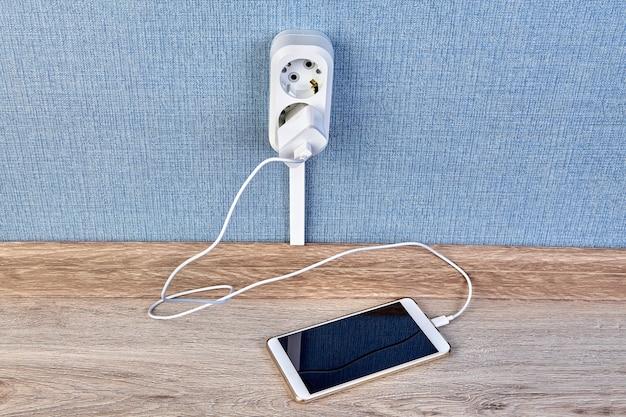Laden des smartphones mit ladegerät und kabel, eingesteckt in steckdose.