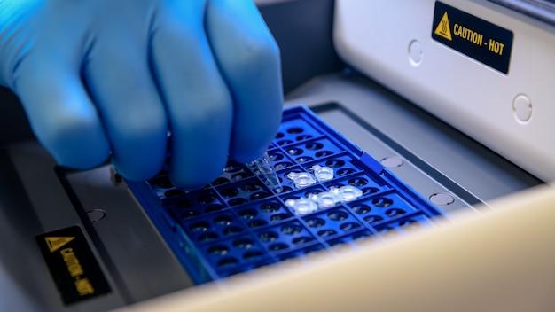 Laden eines dna-röhrchens in eine pcr-thermocycler-maschine (polymerasekettenreaktion) in einem biowissenschaftlichen labor. konzept der wissenschaft, labor und untersuchung von krankheiten.