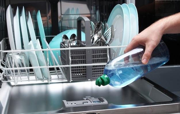 Laden sie die glanzflüssigkeit in den geschirrspüler. füllende spülmaschine des mannes mit glanzflüssigkeit.
