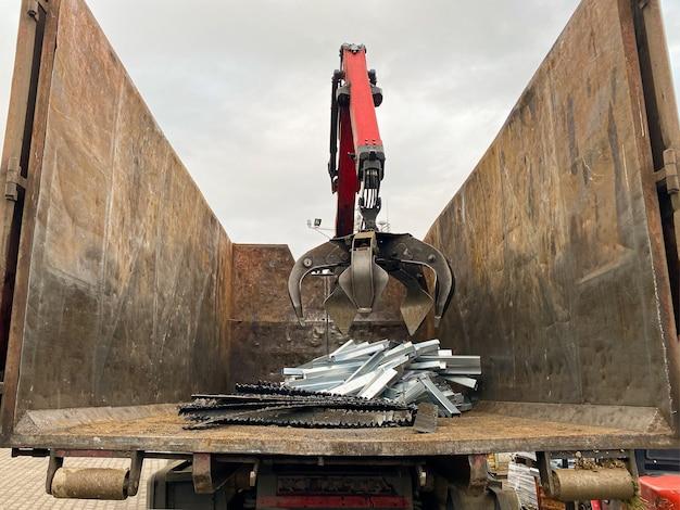 Laden von altmetall in einen lkw crane grabber laden von rostigem metallschrott in das dock