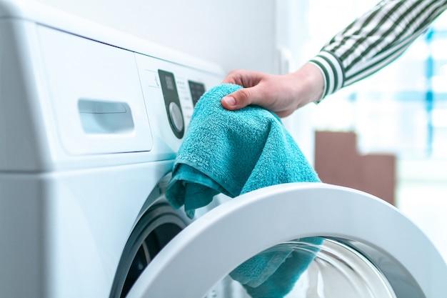 Laden von handtuch, kleidung und wäsche in die waschmaschine. wäsche zu hause waschen. hausarbeit und haushalt
