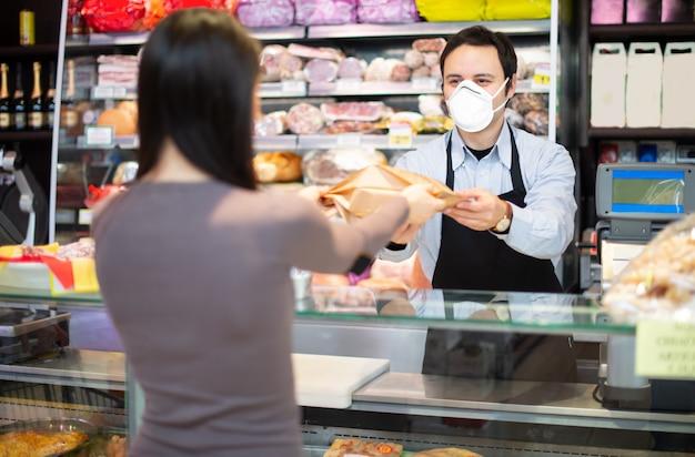 Ladenbesitzer, der einen kunden beim tragen einer maske bedient