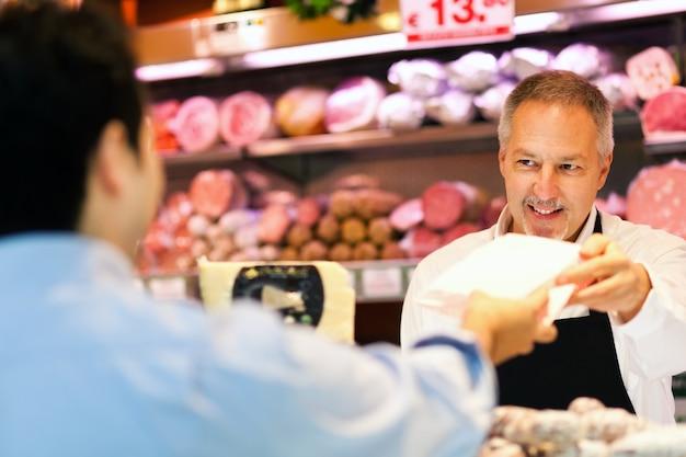 Ladenbesitzer, der einen kunden in einem gemischtwarenladen dient