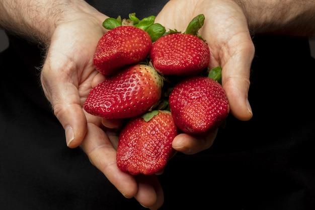 Ladenbesitzer, der frische und natürliche erdbeeren (große erdbeeren) anbietet. vordergrund.