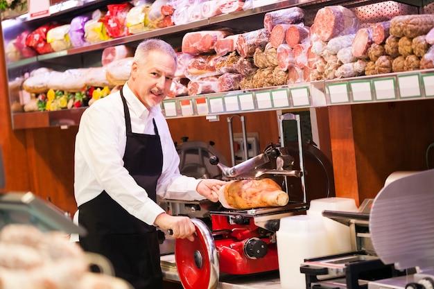 Ladenbesitzer, der schinken in einem gemischtwarenladen schneidet