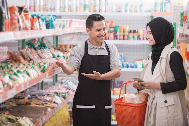 Ladenbesitzer hilft kundin