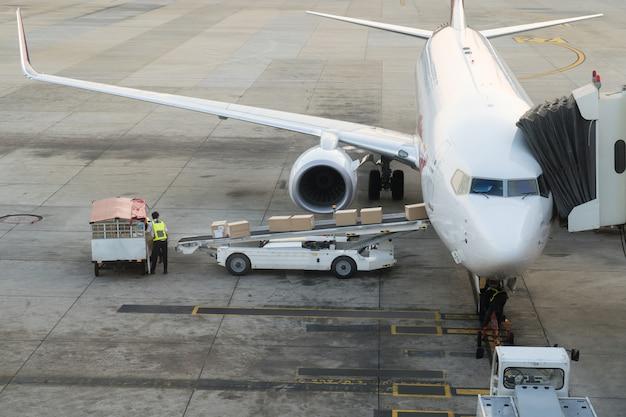 Ladenfracht im flugzeug im flughafen. frachtflugzeugladen oder -entladen im flughafen.