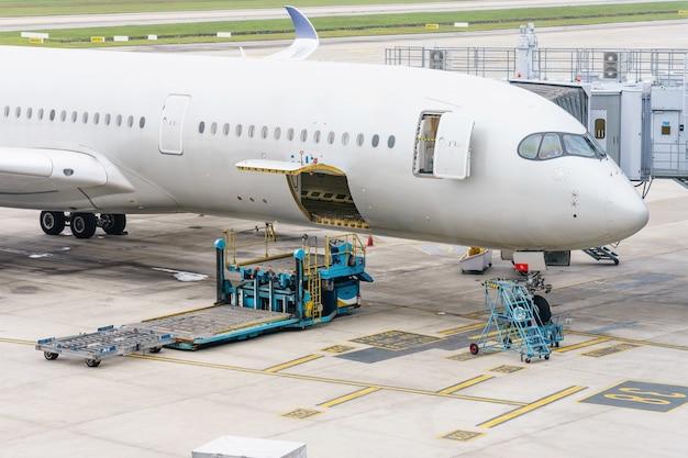 Ladeplattform der luftfracht zum flugzeug. lebensmittel für den flug-check-in und ausrüstung, die vor dem einsteigen in das flugzeug bereitstehen.
