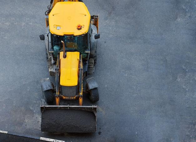 Lader mit boden in schaufeln. straßen- oder rasenreparatur durch die gemeinde. baustelle des traktors. ansicht von oben.