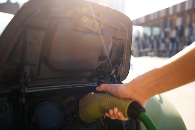 Ladestation für elektrofahrzeuge. männliche hand, die ein elektroauto mit eingestecktem netzkabel auflädt. umweltfreundliches auto für saubere umwelt