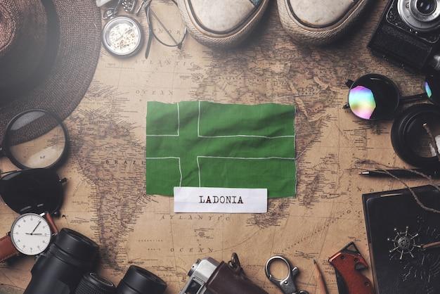 Ladonia-flagge zwischen dem zubehör des reisenden auf alter weinlese-karte. obenliegender schuss