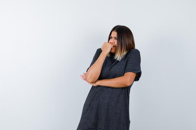 Lady beißt sich in ein schwarzes t-shirt auf die nägel und sieht ängstlich aus. vorderansicht.