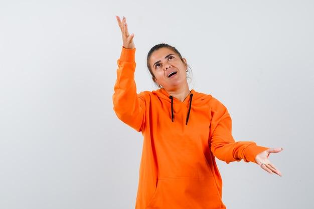 Lady breitet die arme zur seite, während sie in orangefarbenem hoodie aufschaut und erstaunt aussieht