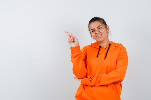 Lady gestikuliert mit hand und zwei fingern im orangefarbenen hoodie und sieht zufrieden aus