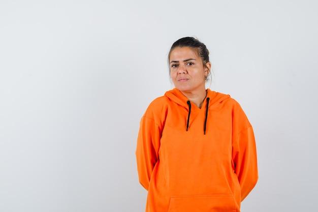 Lady hält die hände hinter dem rücken in orangefarbenem hoodie und sieht selbstbewusst aus