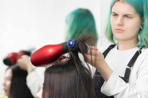 Lady hairstylist trocknet brünette haare mit rotem fön und blauer haarbürste im schönheitssalon