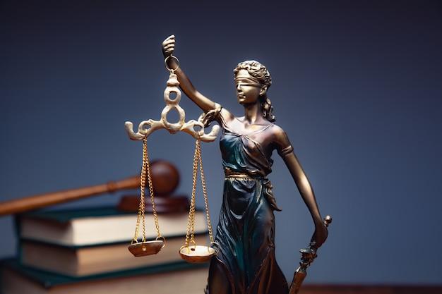 Lady justice mit büchern auf dem tisch