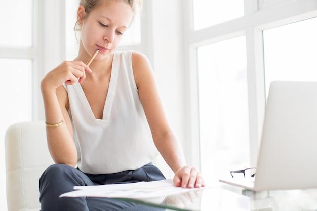 Lady thinking und arbeiten mit dokumenten am fenster