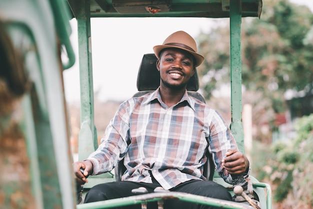 Lächeln afrikanischer männlicher arbeiter, der bagger auf baustelle betreibt
