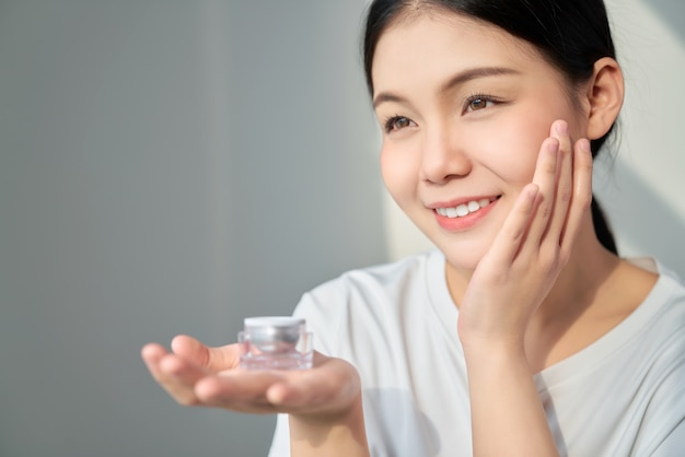 Lächeln asiatische frau hautschönheit und hand, die eine produktcremeflasche für spa-produkte und make-up hält. die haut ist glatt und schön.
