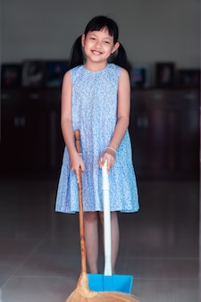 Lächeln asiatisches kleines mädchen, das mit besen und kehrschaufel im haus fegt