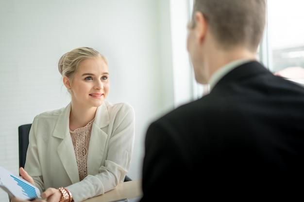 Lächeln der geschäftsfrau, die über bericht mit chef am schreibtisch im büro spricht