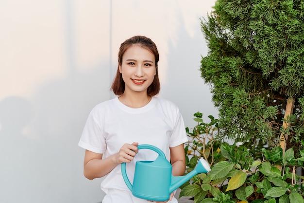 Lächeln der jungen asiatin, die pflanzen gießt