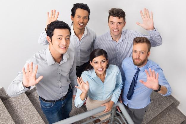 Lächeln geschäftsleute winken auf bürotreppenhaus