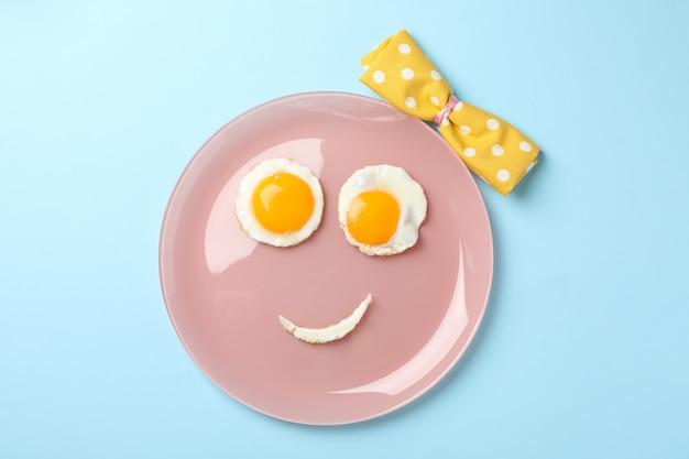 Lächeln gesicht gemacht von platte mit spiegeleiern auf blauem hintergrund, draufsicht