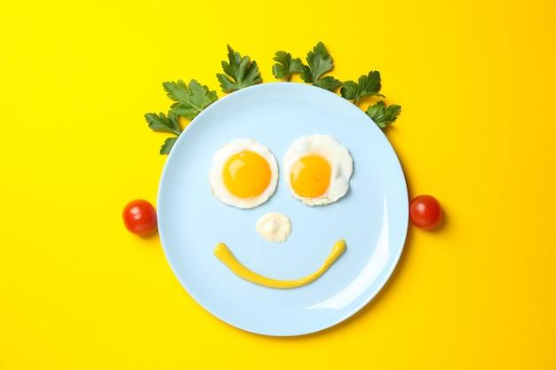 Lächeln gesicht gemacht von platte mit spiegeleiern auf gelbem hintergrund, draufsicht