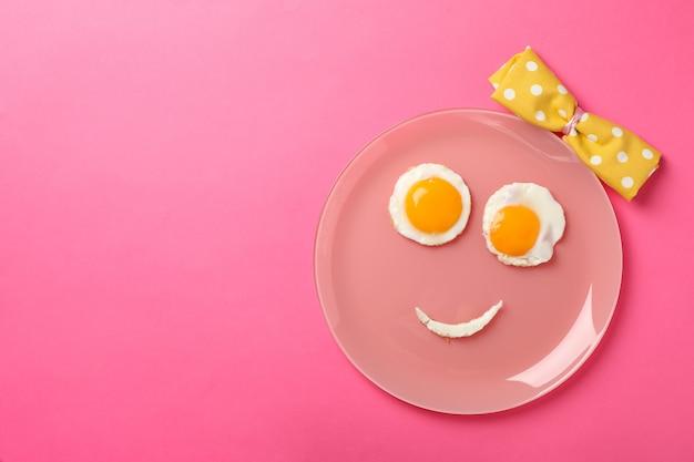 Lächeln gesicht gemacht von platte mit spiegeleiern auf rosa hintergrund, draufsicht
