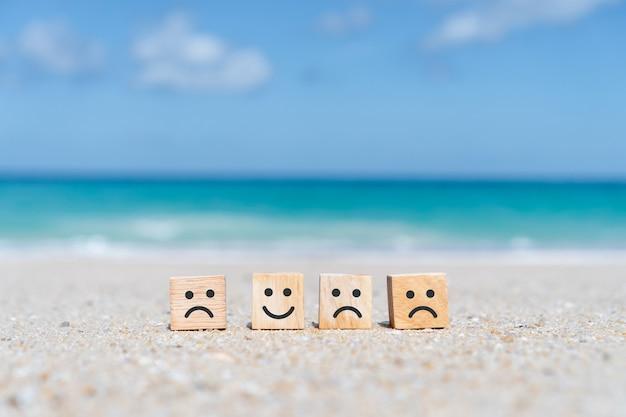 Lächeln gesicht und wagen symbol auf holzwürfel. optimistische person oder personen, die sich beim einkaufen im inneren und in der servicebewertung fühlen.