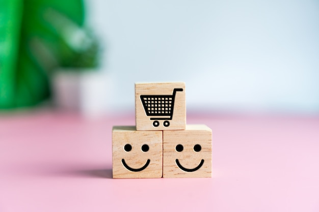 Lächeln gesicht und wagen symbol auf holzwürfel. optimistische person oder personen, die sich beim einkaufen innerlich fühlen und service-bewertung, zufriedenheitskonzept.