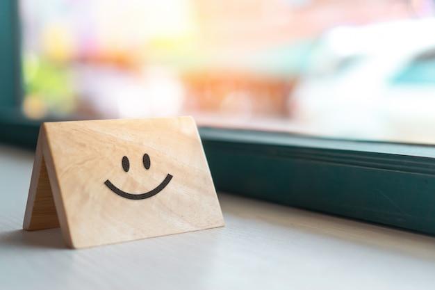 Lächeln gesichtssymbol auf holzschild. optimistische person oder personen, die sich innerlich fühlen und servicebewertung, zufriedenheitskonzept.