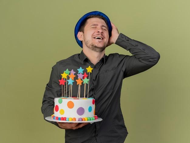 Lächeln mit jungem party-kerl der geschlossenen augen, der schwarzes hemd und blauen hut hält kuchen hält hand auf hut lokalisiert auf olivgrün