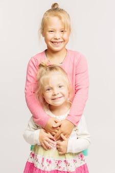 Lächeln mit zwei blondes kleinen mädchen