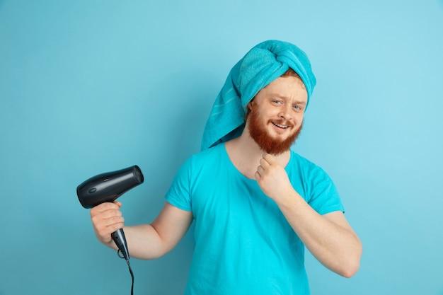 Lächeln. porträt des jungen kaukasischen mannes in seiner schönheitstag- und hautpflege-routine. männliches modell mit natürlichem rotem haar, das seinen bart trocken bläst und frisur bildet. körper- und gesichtspflege, natürliches schönheitskonzept.