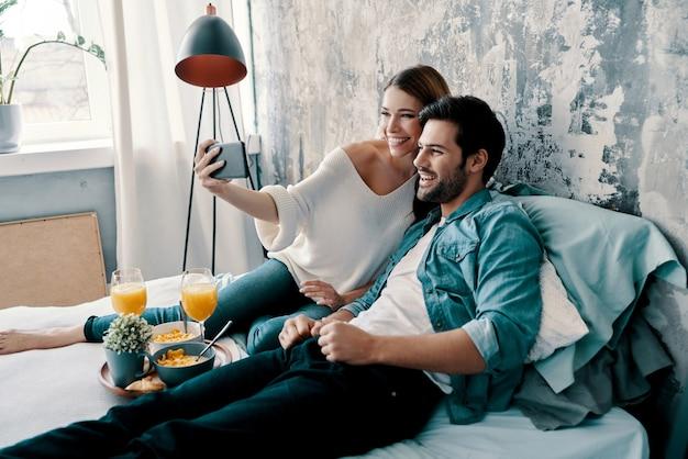 Lächeln! schönes junges paar, das selfie macht und lächelt, während es zeit im bett zu hause verbringt