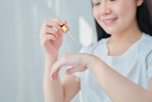 Lächeln sie asiatische frau, die ein produkt serumflasche für spa-produkte und make-up hält. die haut ist glatt und schön.