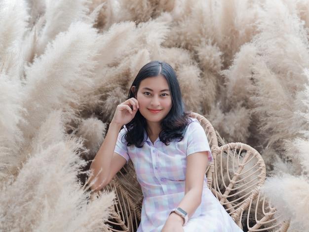 Lächeln sie asiatische frau in freizeitkleidung sitzen im trockenen, weichen, flauschigen grasblumengarten, glückliches mädchen positives denken entspannen sich im urlaub