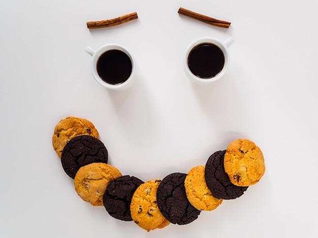 Lächeln sie auf dem produkttisch. kaffee, kekse und zimt.