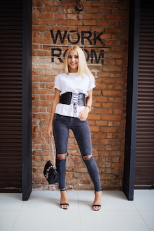 Lächeln sie glückliches blondes mädchen nahe alter backsteinmauer