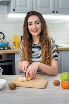 Lächeln sie junge frau, die frischen salat mit obst in der küche kocht. gesunder lebensstil. diät