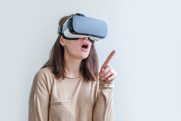 Lächeln sie junge frau, die unter verwendung des vr-brillenhelmkopfsatzes der virtuellen realität auf weißem tisch trägt