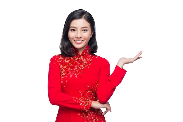 Lächeln sie vietnamesische frau im traditionellen ao dai kleid und stellen sie auf weißem hintergrund vor.