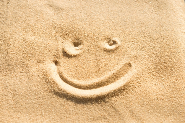 Lächeln sie zeichenzeichnung auf dem strandsand