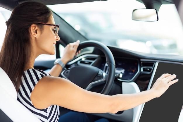 Lächeln und autofahren. geschäftsfrau mit brille, die morgens beim autofahren lächelt