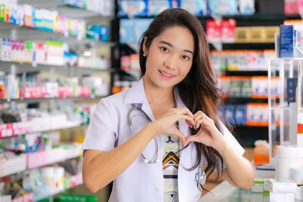 Lächeln und glücklich vom asiatischen weiblichen apotheker, der herzgeste mit zwei händen in der apotheke zeigt