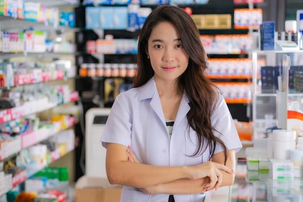 Lächeln und glücklich vom asiatischen weiblichen apotheker in der apotheke